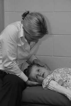 Chiropractor checking child's spine
